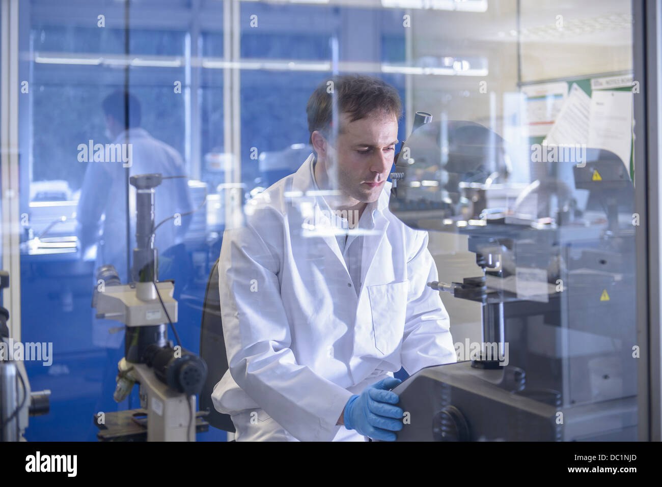 Scientist working on specialist equipment in laboratory - Stock Image