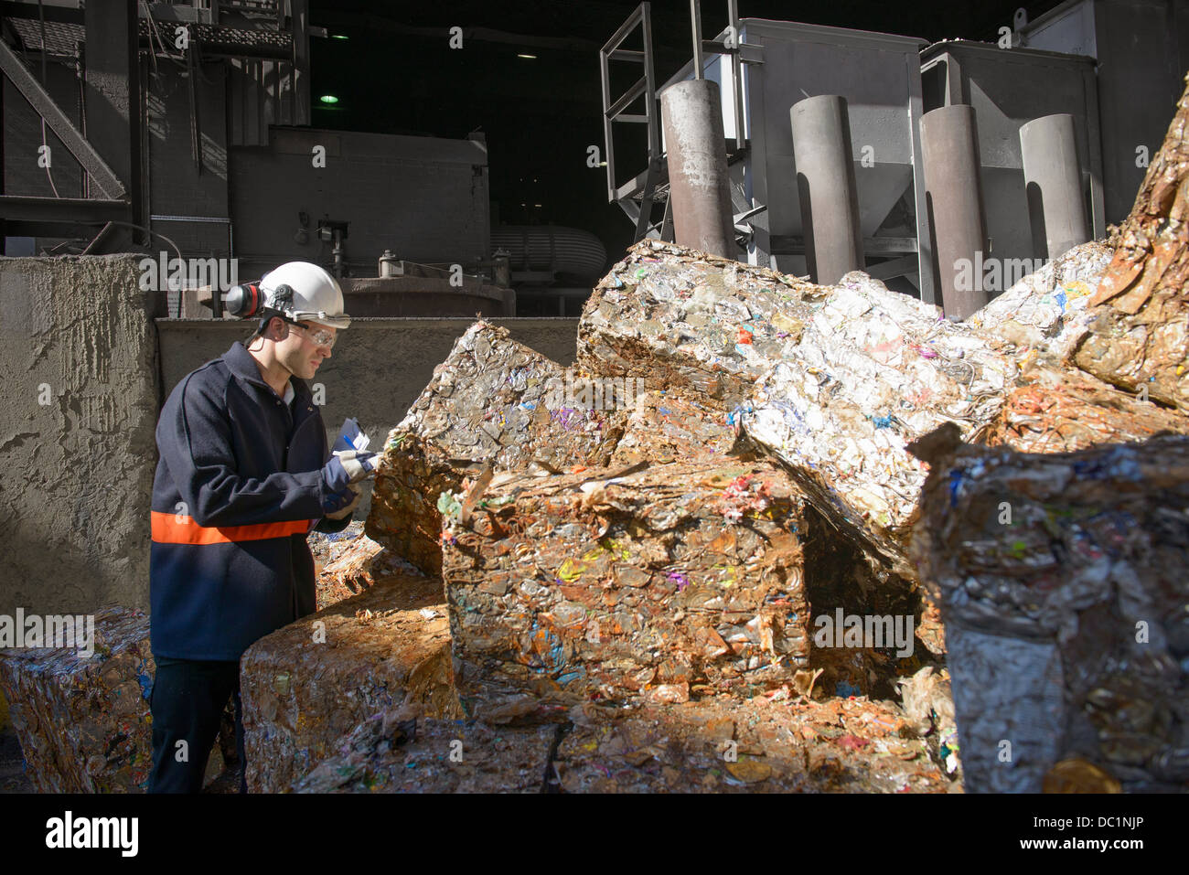 Steel worker examining scrap metal bales outside foundry - Stock Image