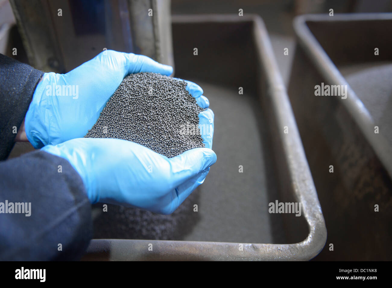 Worker with handful of steel shot in steel foundry - Stock Image