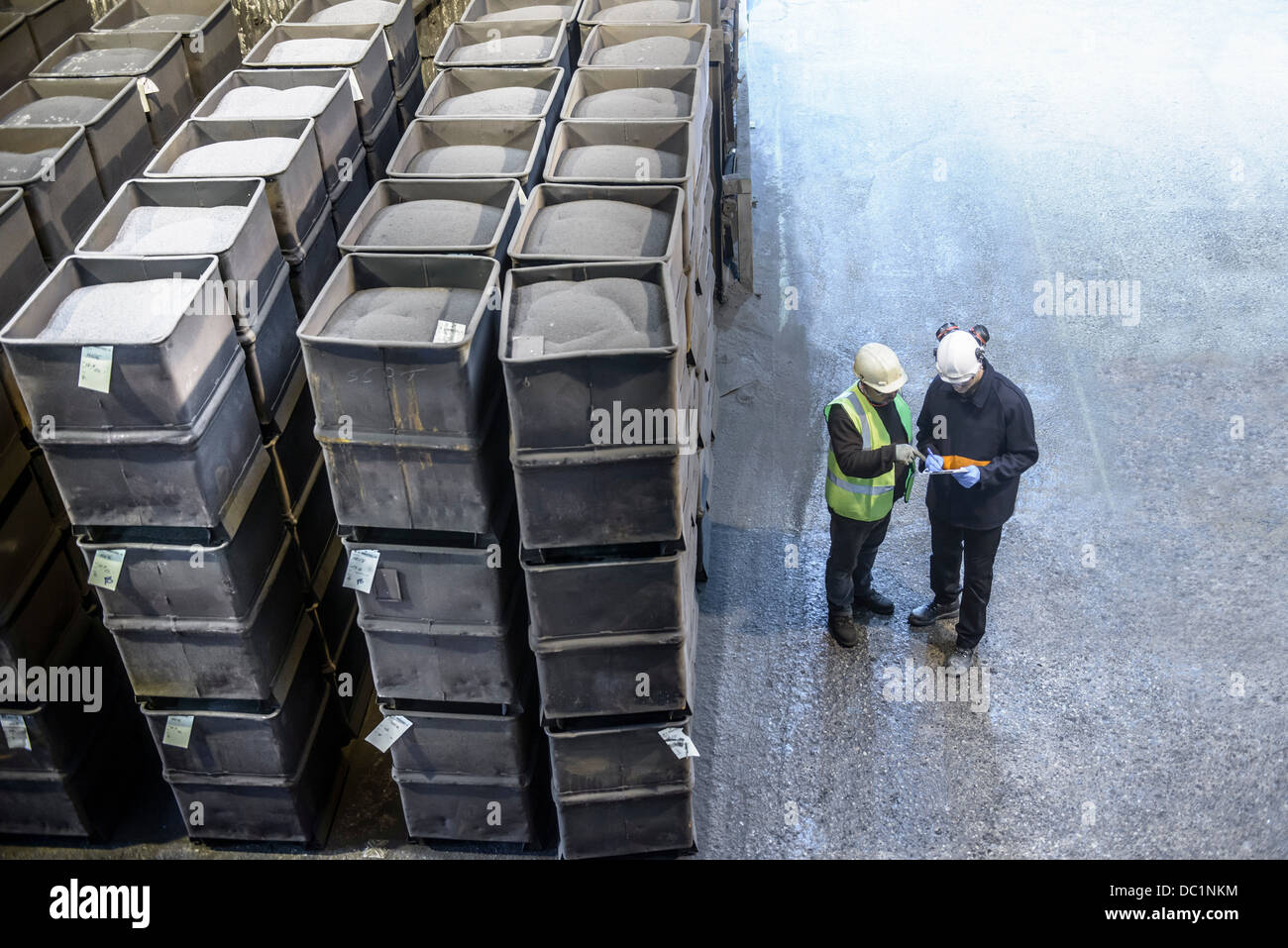 Workers monitoring crates of steel shot in steel foundry Stock Photo