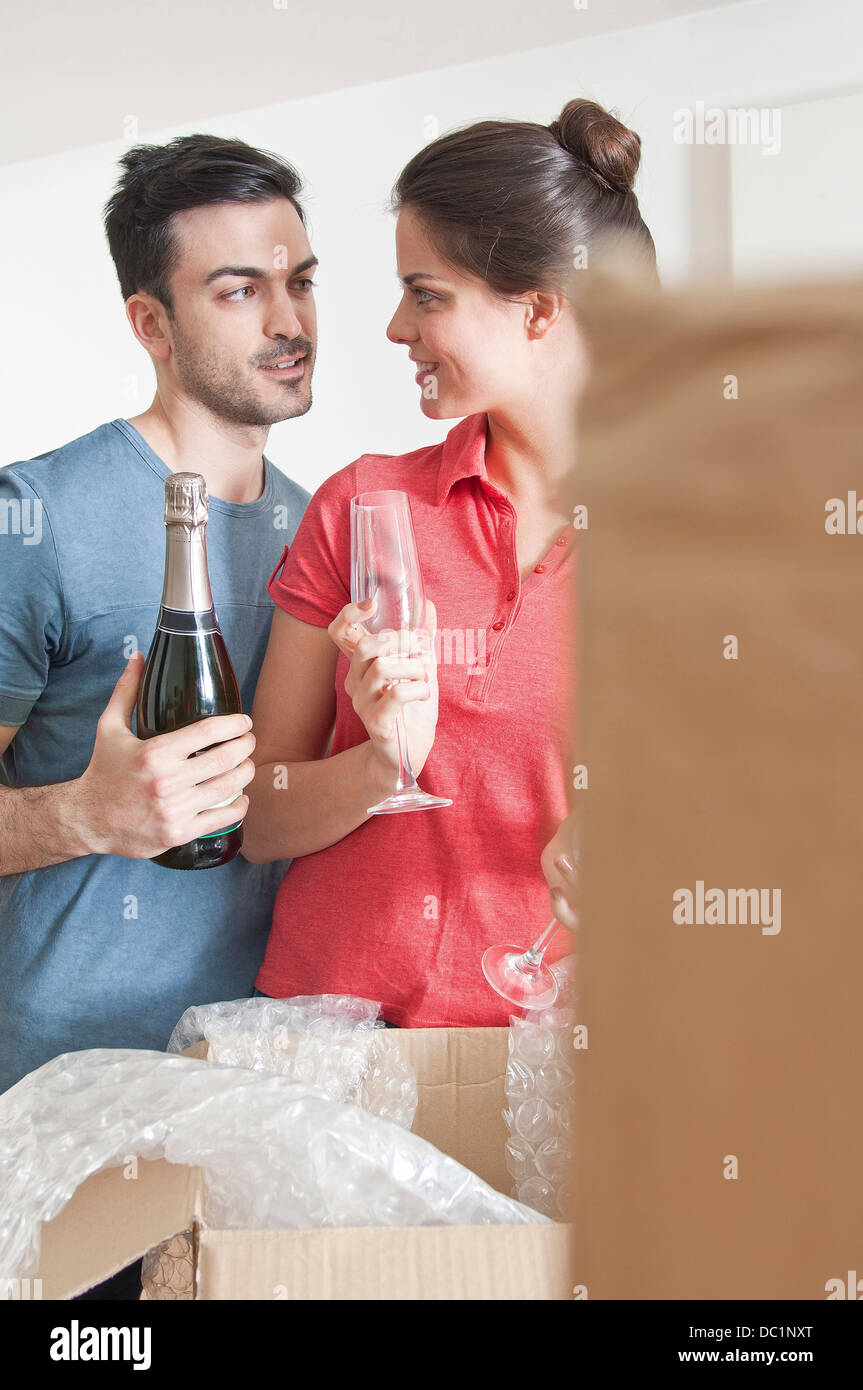 Young couple celebrating with champagne amongst cardboard boxes - Stock Image