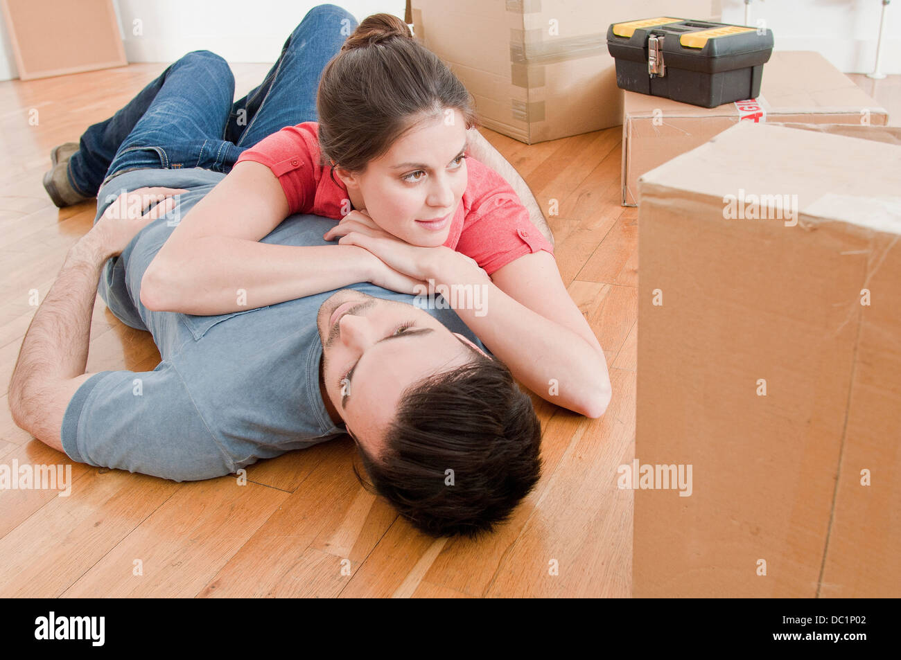Young couple taking a break amongst cardboard boxes - Stock Image