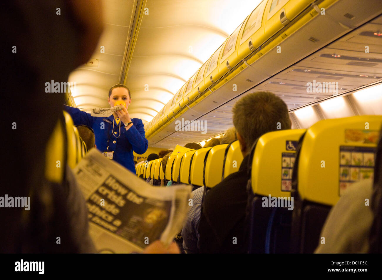 Safety demonstration aboard a Ryanair flight some passengers ignore the information carry on reading newspaper - Stock Image