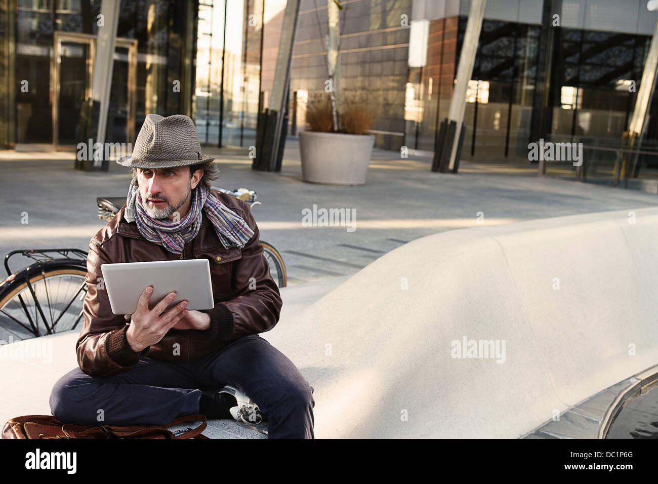 Mid adult man using digital tablet in city - Stock Image