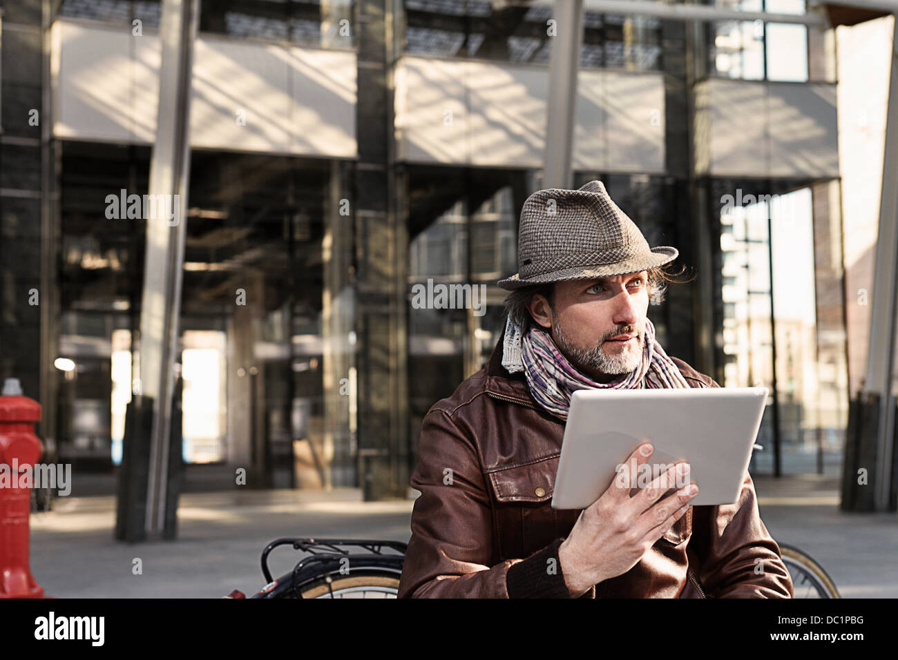 Mid adult man using digital tablet and looking away - Stock Image