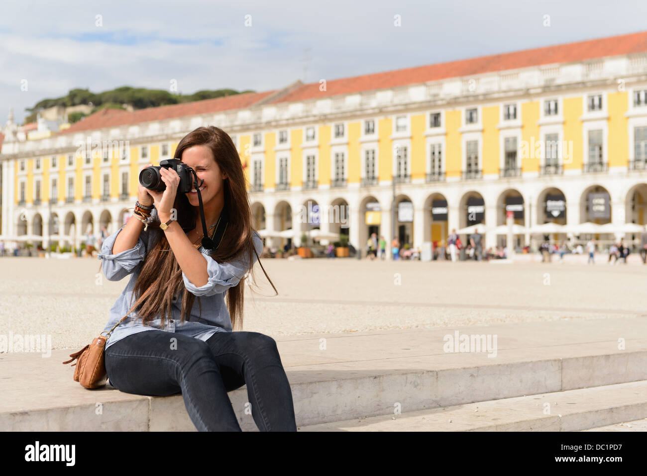 Young female tourist photographing in Rossio Square, Lisbon, Portugal - Stock Image