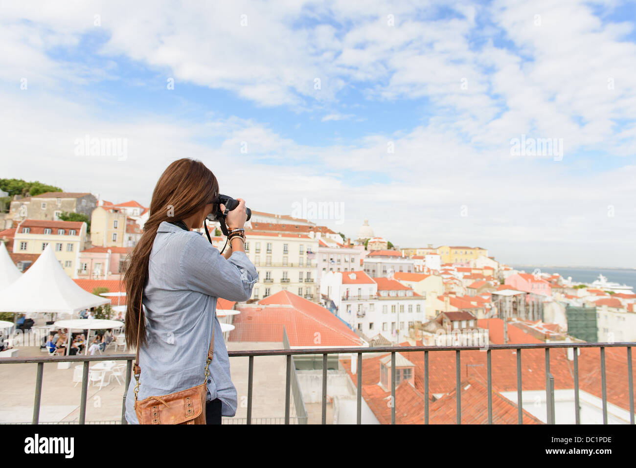 Young female tourist photographing in Alfama District, Lisbon, Portugal - Stock Image