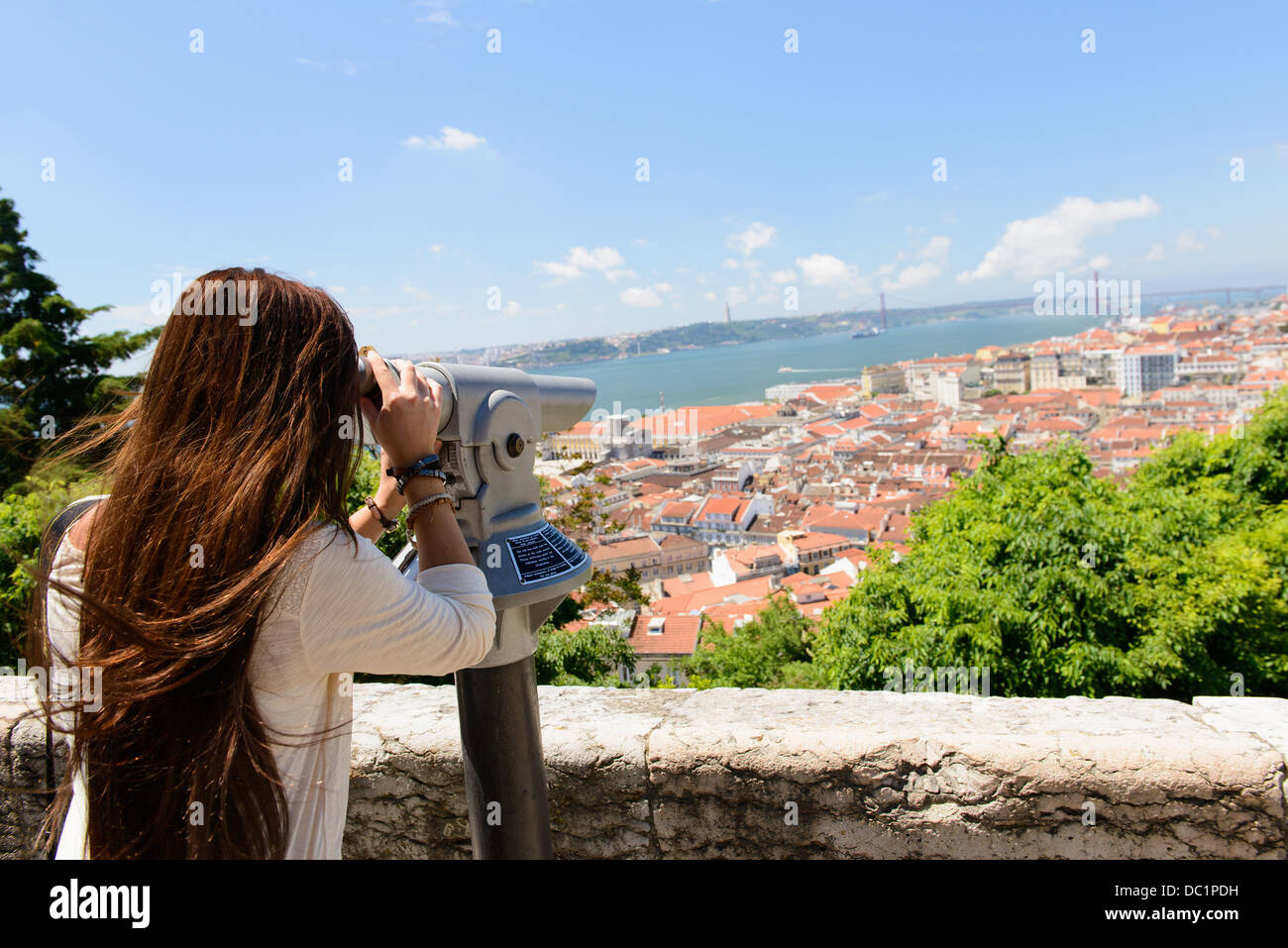 Young female tourist looking through coin operated binoculars in Lisbon, Portugal - Stock Image