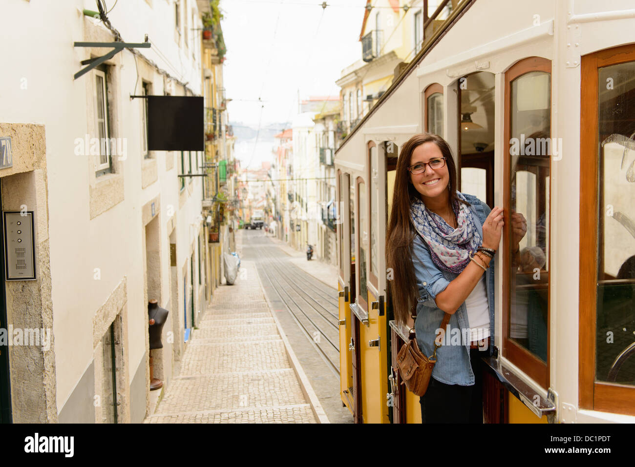 Portrait of young female tourist riding tram in Lisbon, Portugal - Stock Image
