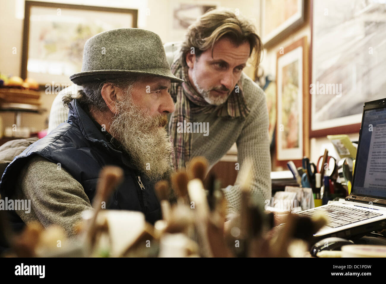 Senior and mid adult man using laptop in antique shop - Stock Image