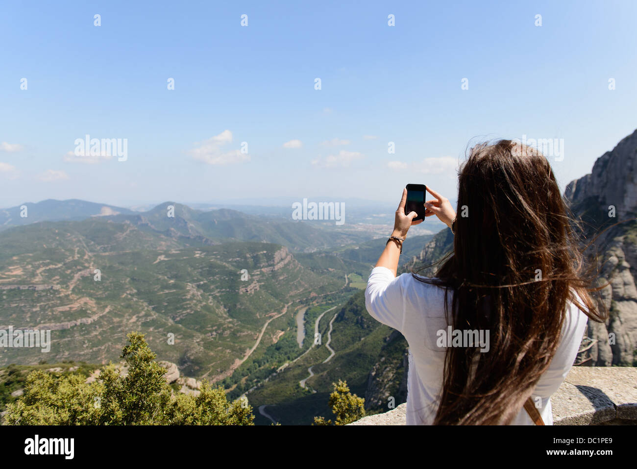 Young female tourist photographing the view of montserrat, Spain - Stock Image