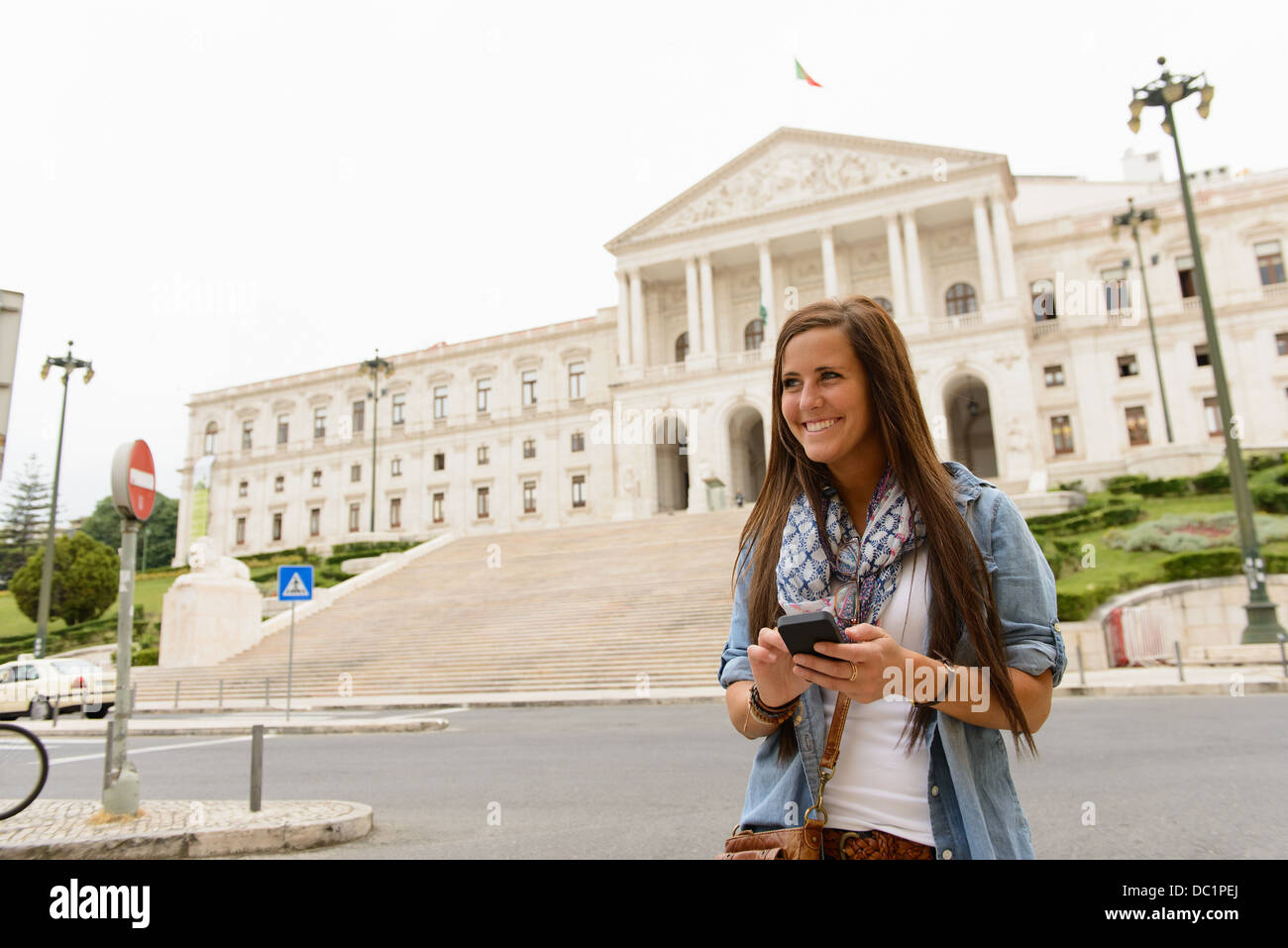 Female tourist using smartphone outside Palicio de Sao Bento, Lisbon, Portugal - Stock Image