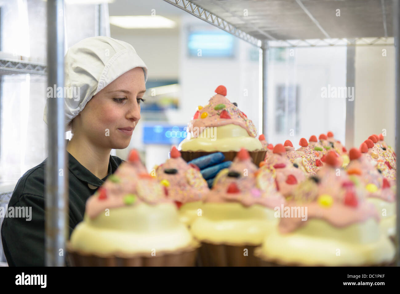 Chocolatier arranging giant chocolate cupcakes in sweet factory Stock Photo