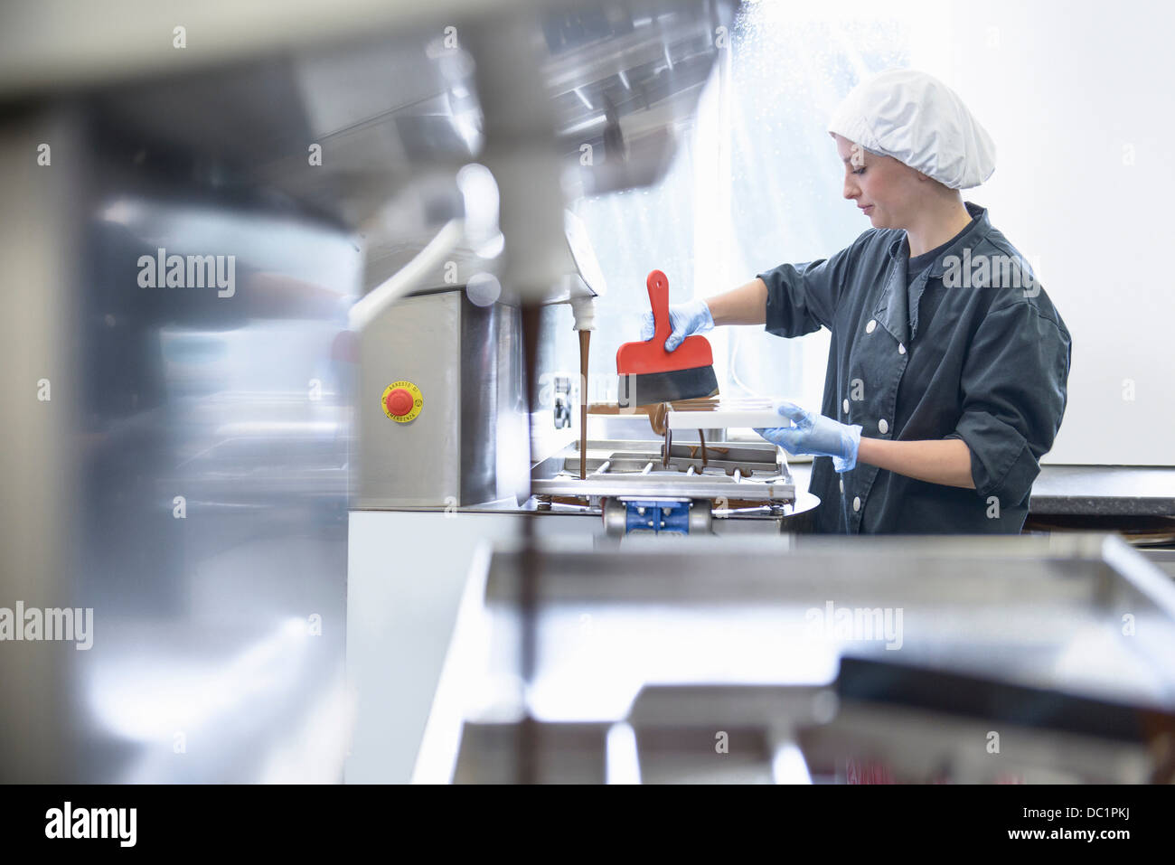 Chocolatier smoothing chocolate in moulds in sweet factory - Stock Image