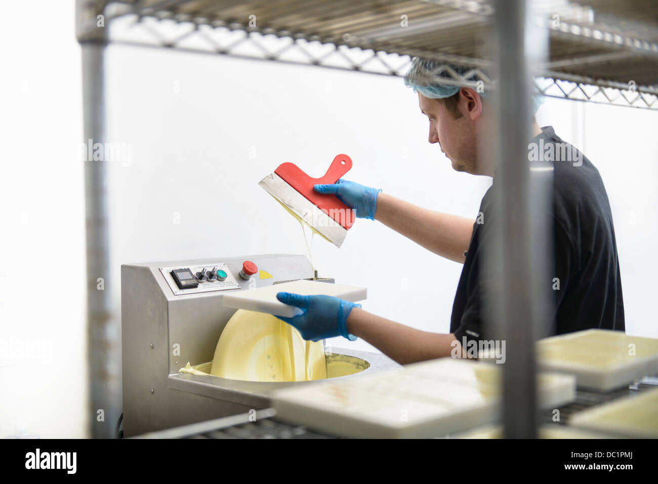 Chocolatier smoothing white chocolate in sweet factory - Stock Image