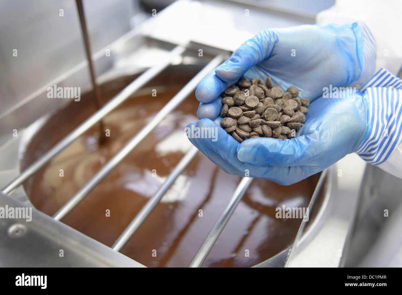 Chocolatier with a handful of chocolate pieces in sweet factory - Stock Image