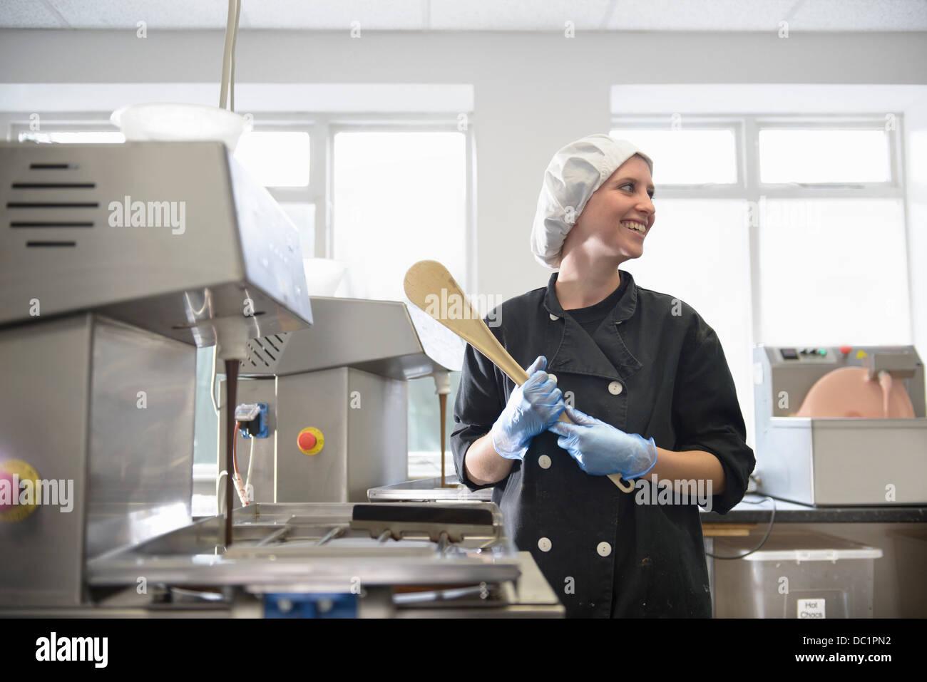 Candid portrait of chocolatier in sweet factory - Stock Image