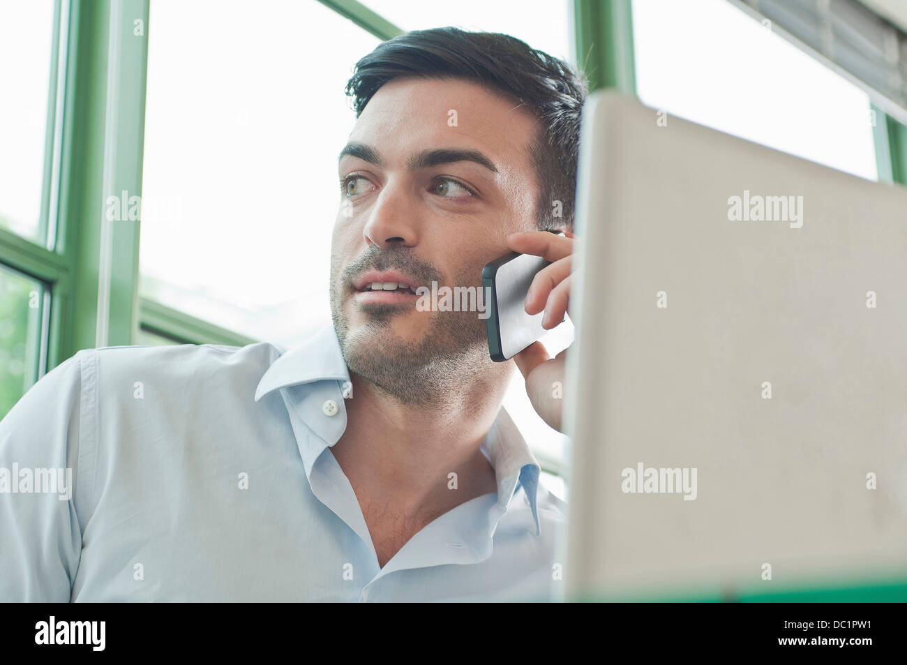 Close up of young male office worker talking on mobile phone - Stock Image