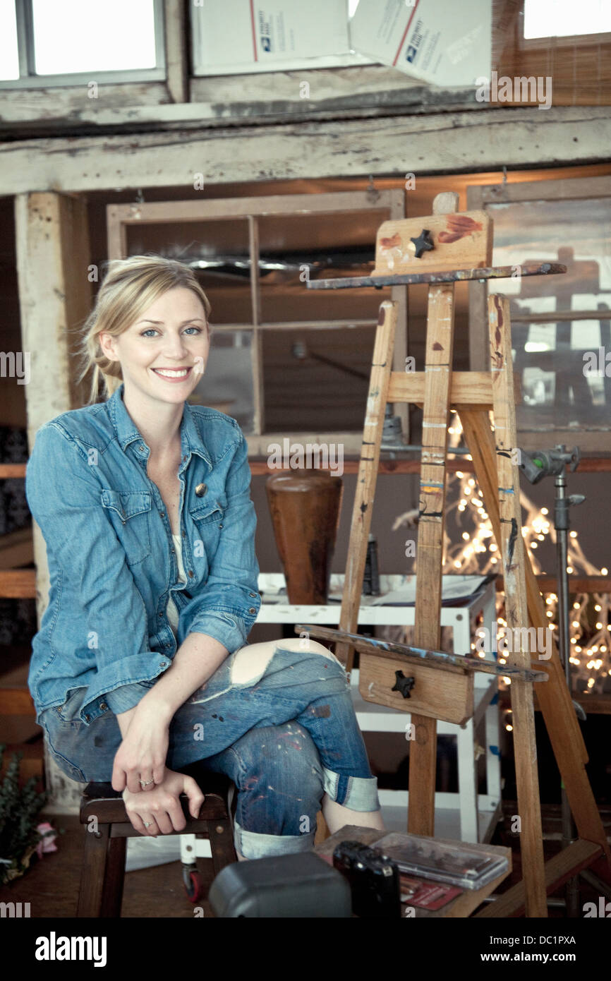 Mid adult woman sitting in artist's studio, portrait - Stock Image