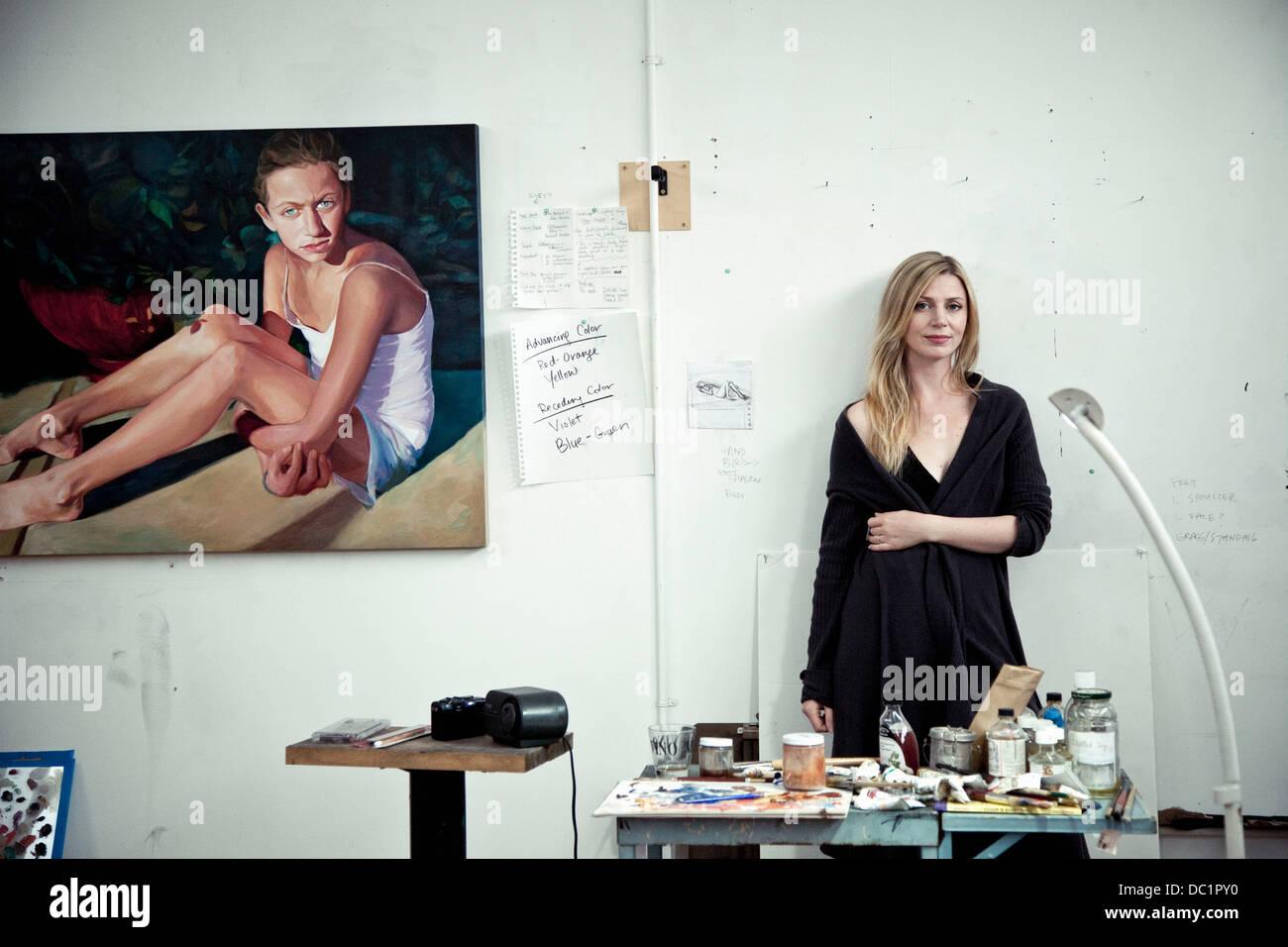 Mid adult woman standing in artist's studio, portrait - Stock Image