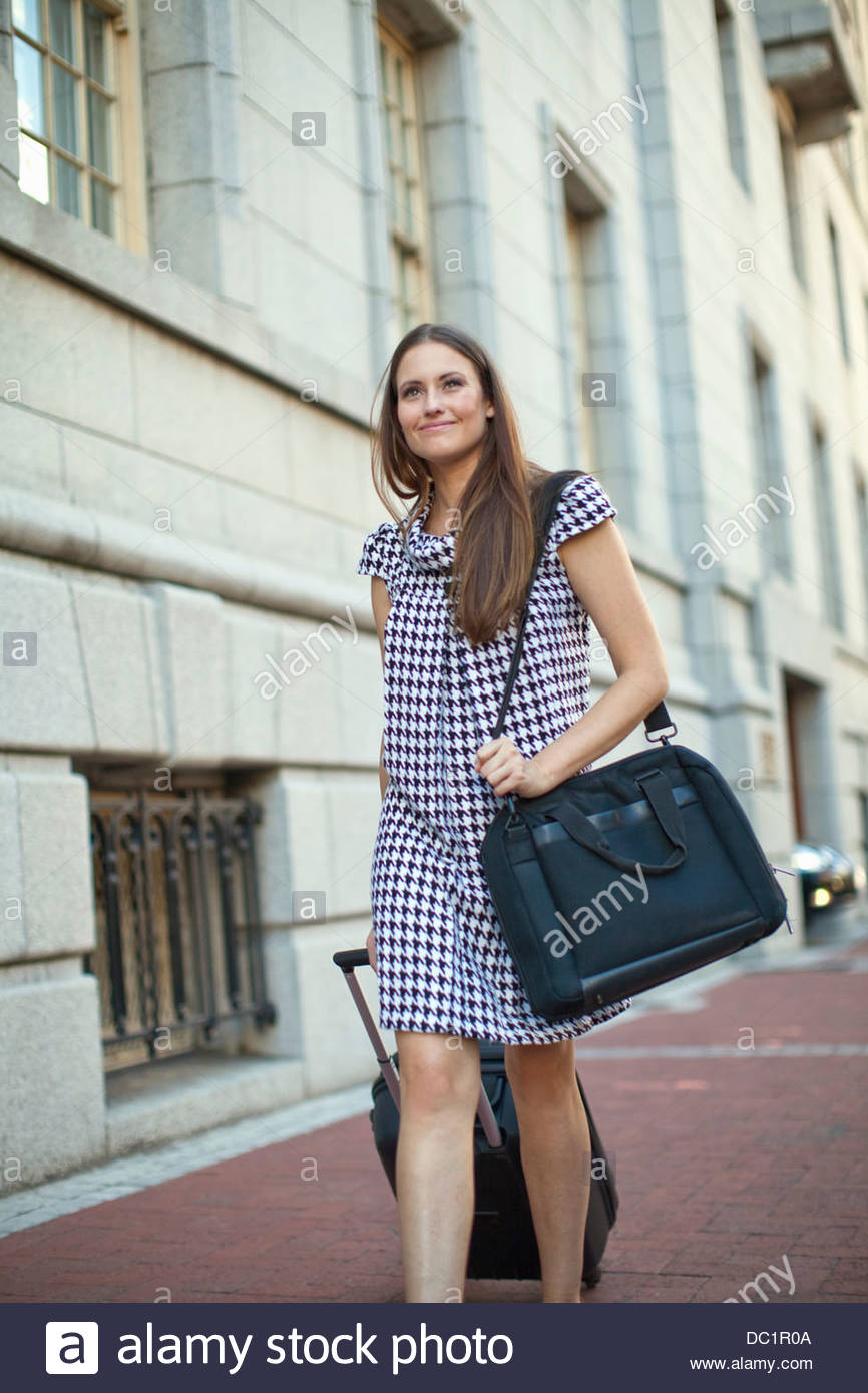 Young woman pulling wheeled case on sidewalk - Stock Image