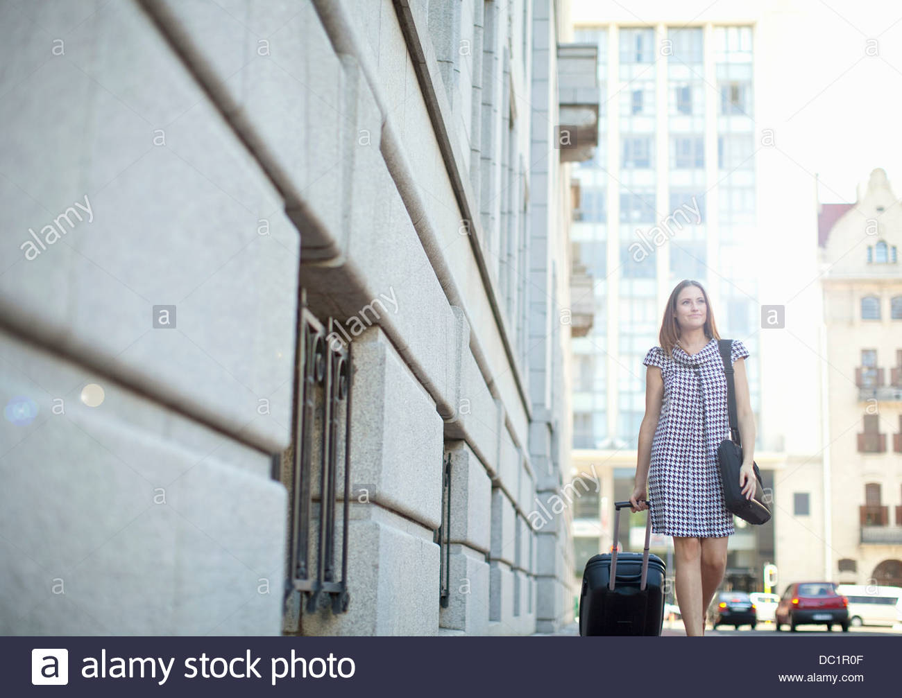 Young woman pulling wheeled case on street - Stock Image
