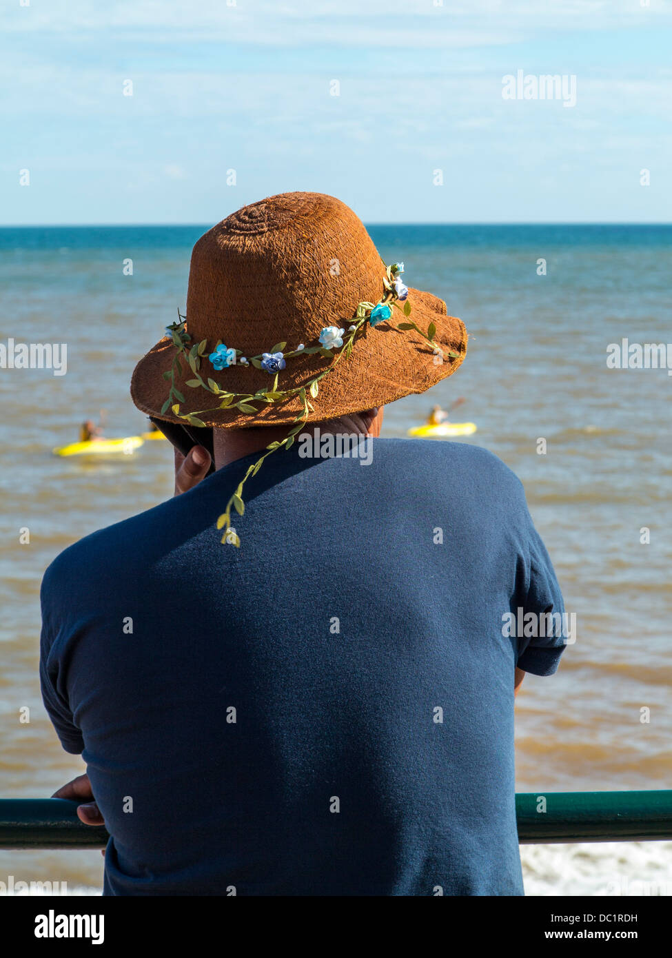 Man on phone with garland around his hat on Sidmouth seafront, Devon, England - Stock Image