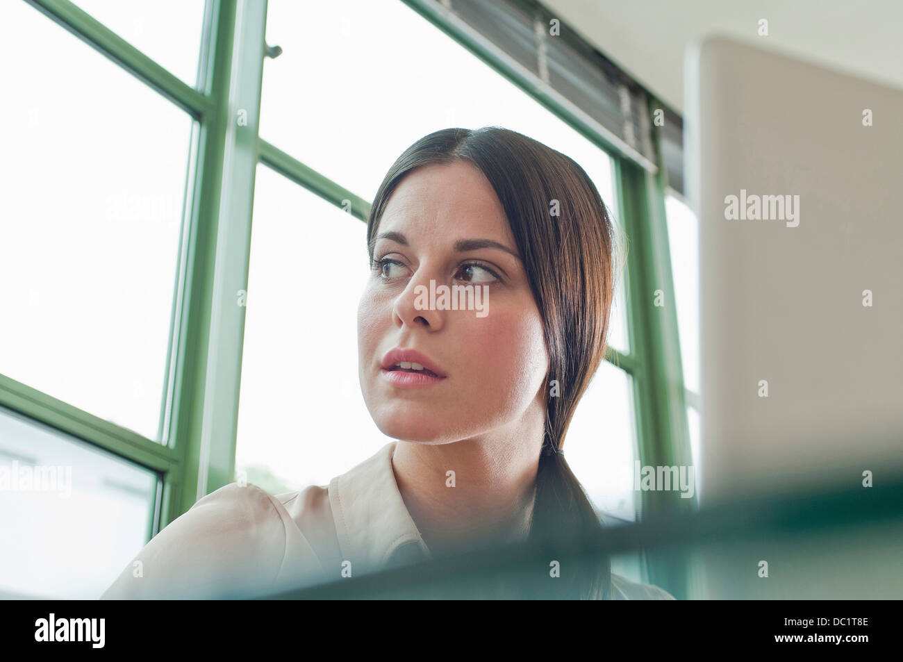 Young female office worker looking out of window - Stock Image