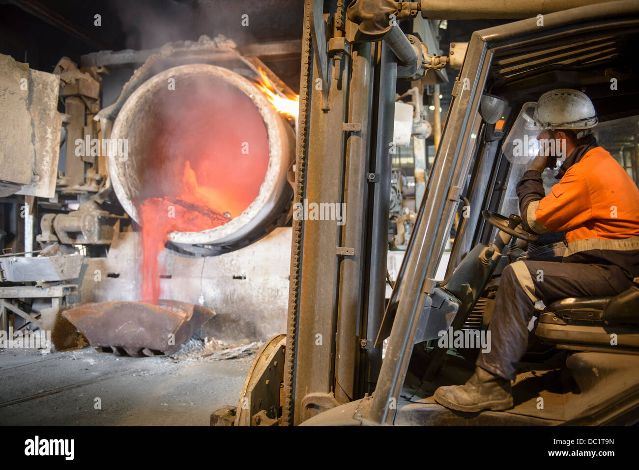 Worker monitoring molten aluminum running into mold - Stock Image
