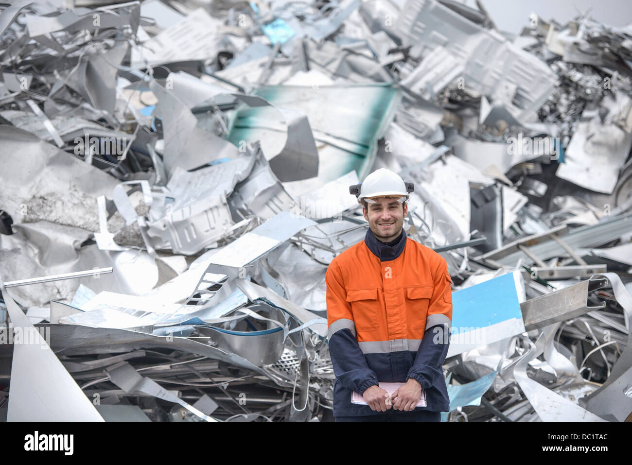Portrait of worker in front of scrap aluminum - Stock Image