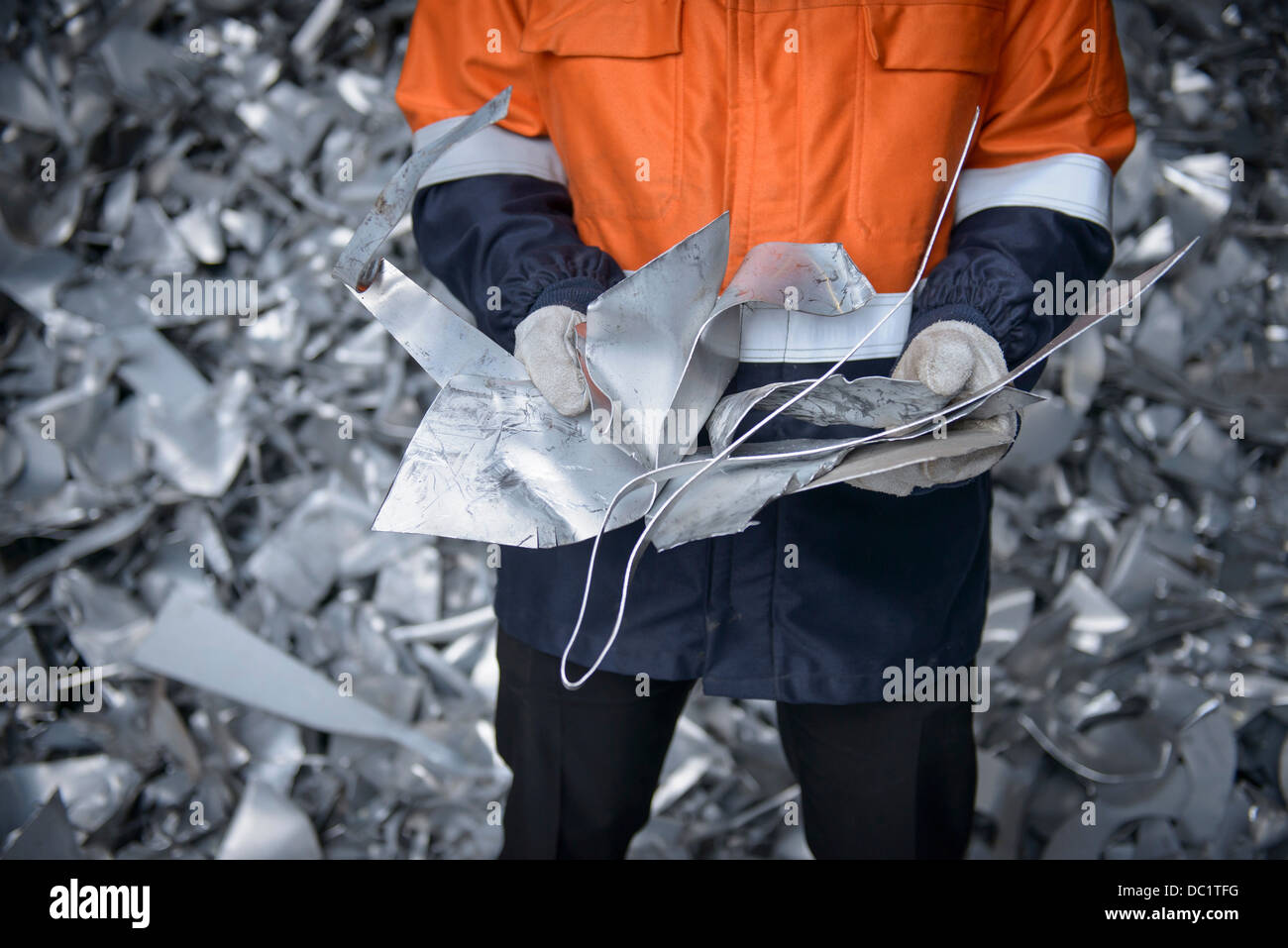 Close up of worker holding scrap aluminum - Stock Image