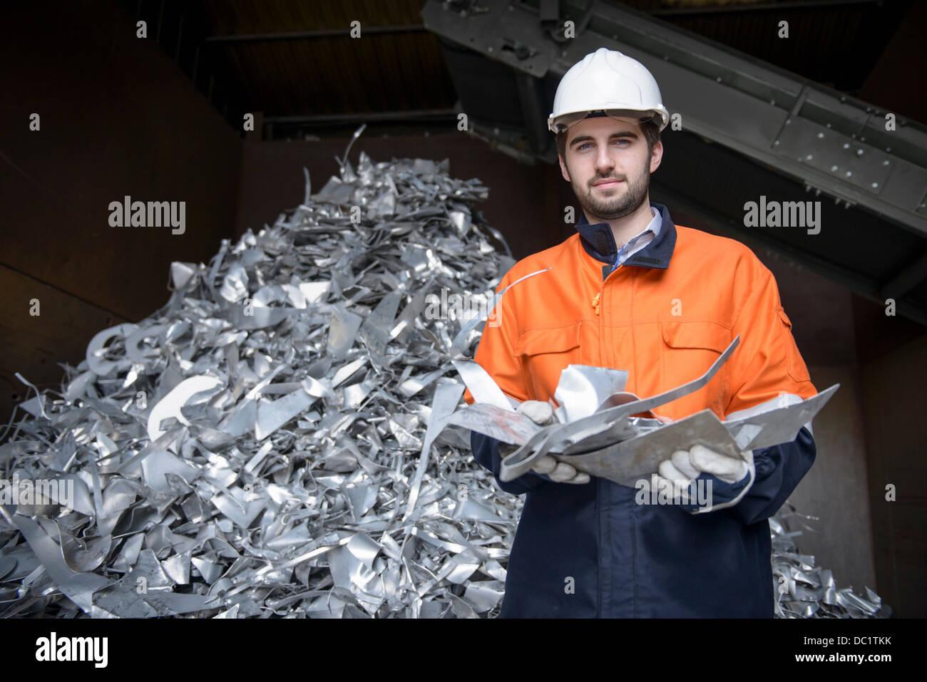 Portrait of worker holding scrap aluminum - Stock Image