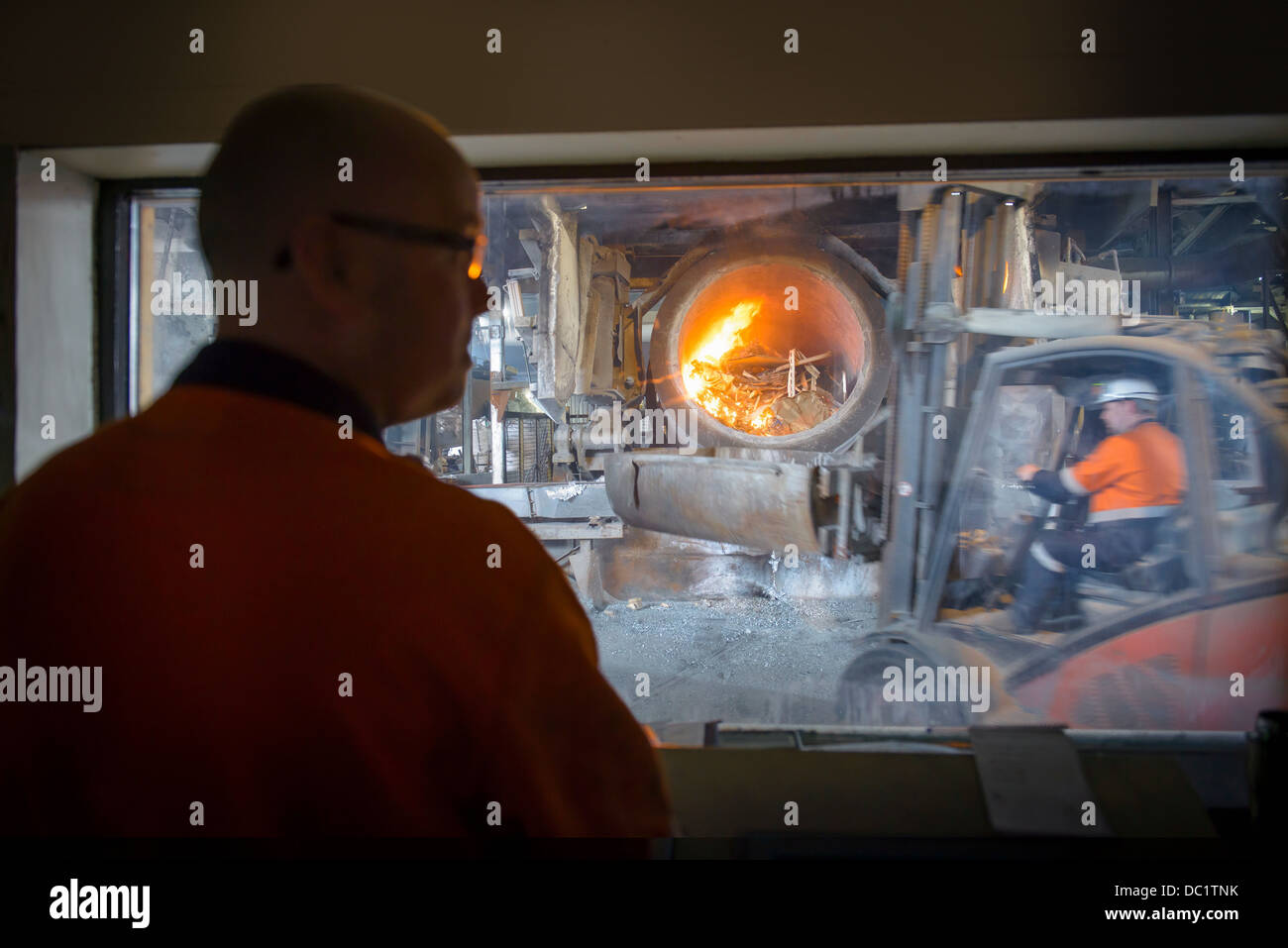 Controller watching furnace at aluminum recycling plant - Stock Image