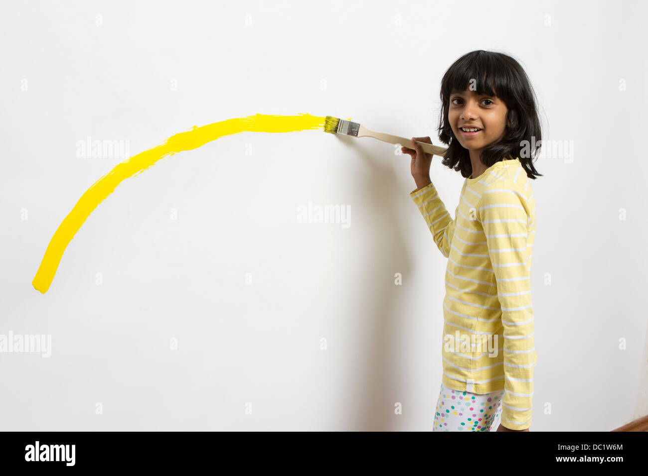 Portrait of girl painting yellow curve on wall - Stock Image