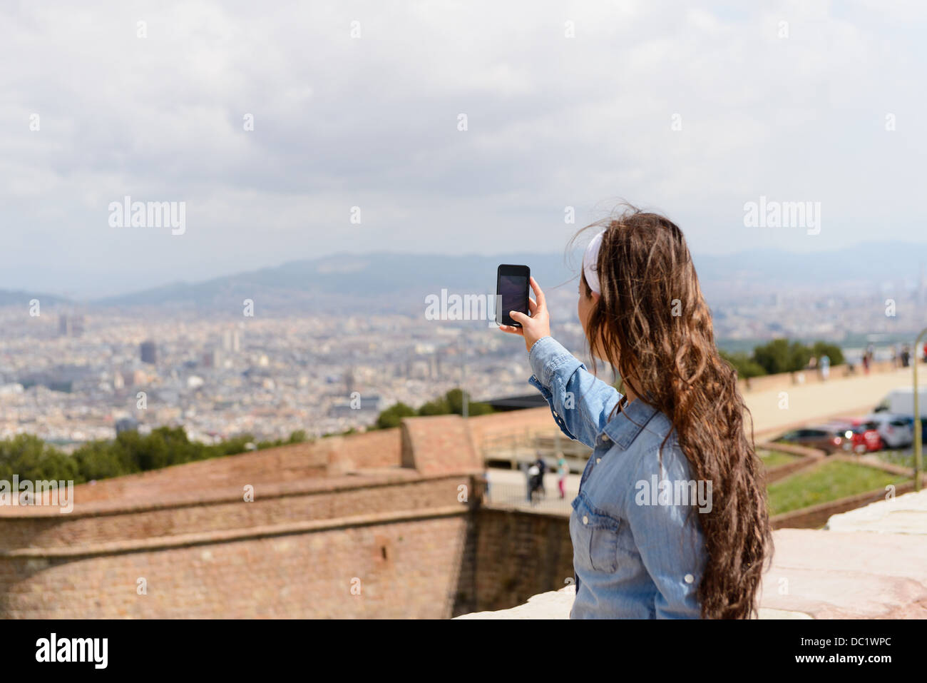 Young female tourist photographing view of Barcelona city, Spain - Stock Image