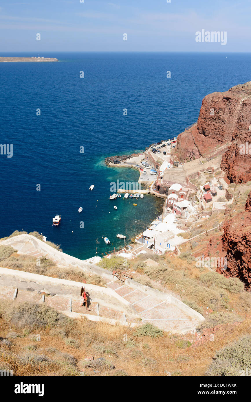 Distant view of female tourist walking down steps, Oia, Santorini, Greece - Stock Image
