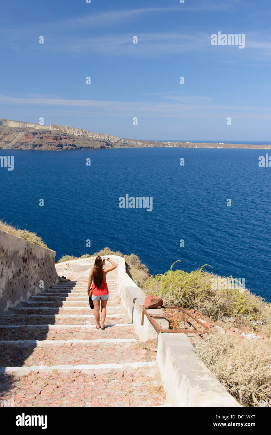 Female tourist walking down steps, Oia, Santorini, Greece - Stock Image