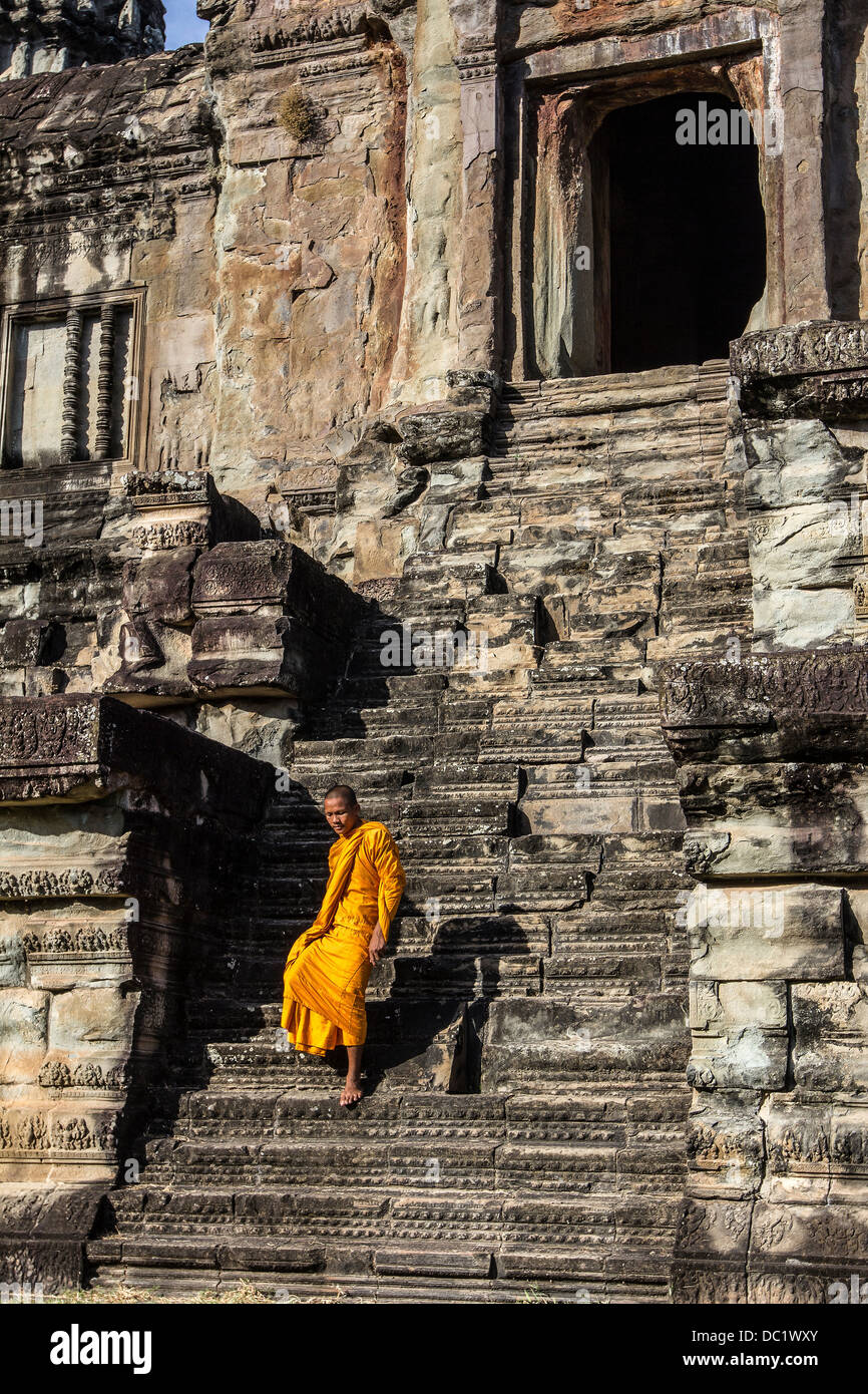Young Buddhist monk walking down steps at temple in Angkor Wat, Siem Reap, Cambodia Stock Photo