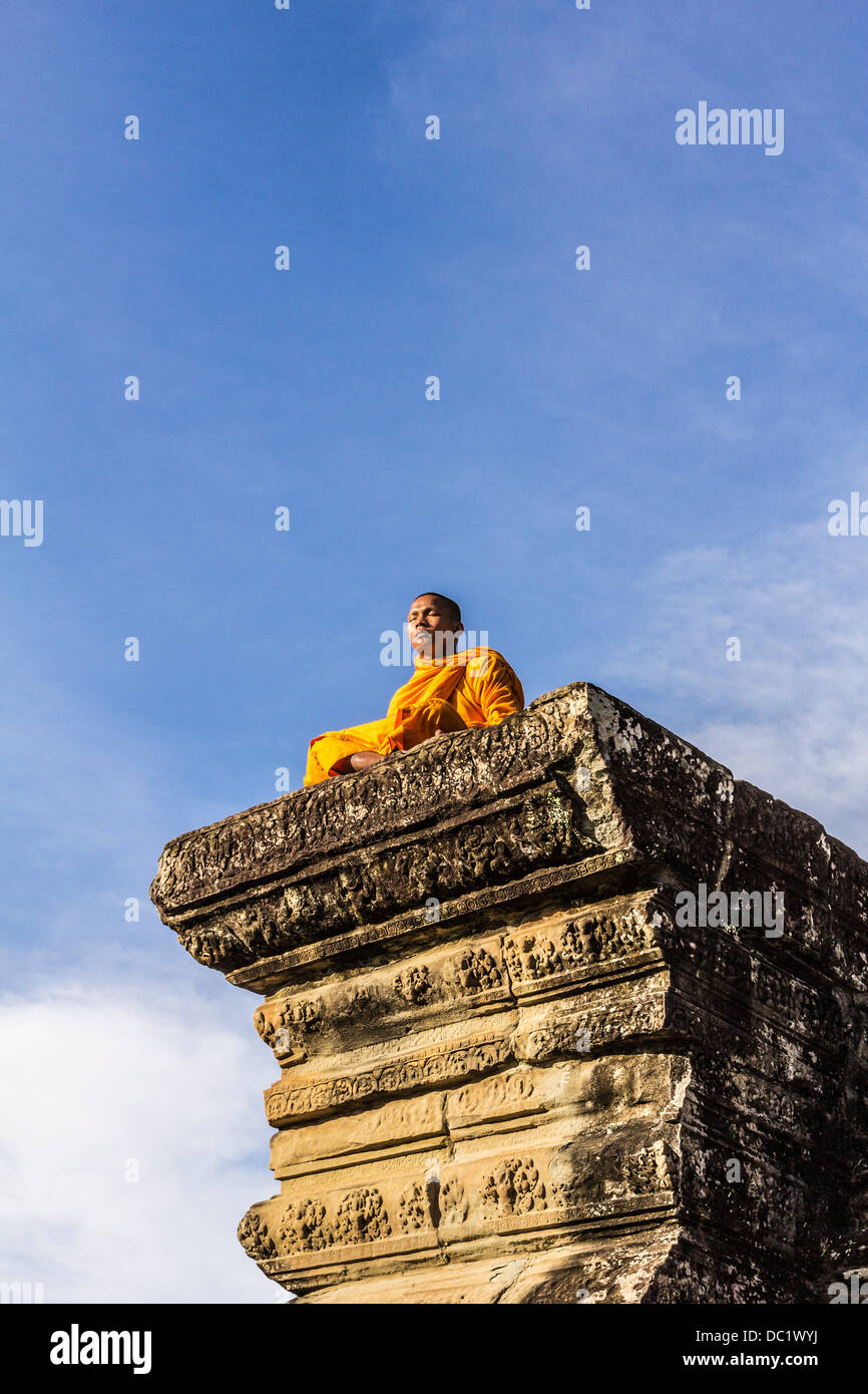 Young Buddhist monk sitting outside temple in Angkor Wat, Siem Reap, Cambodia - Stock Image