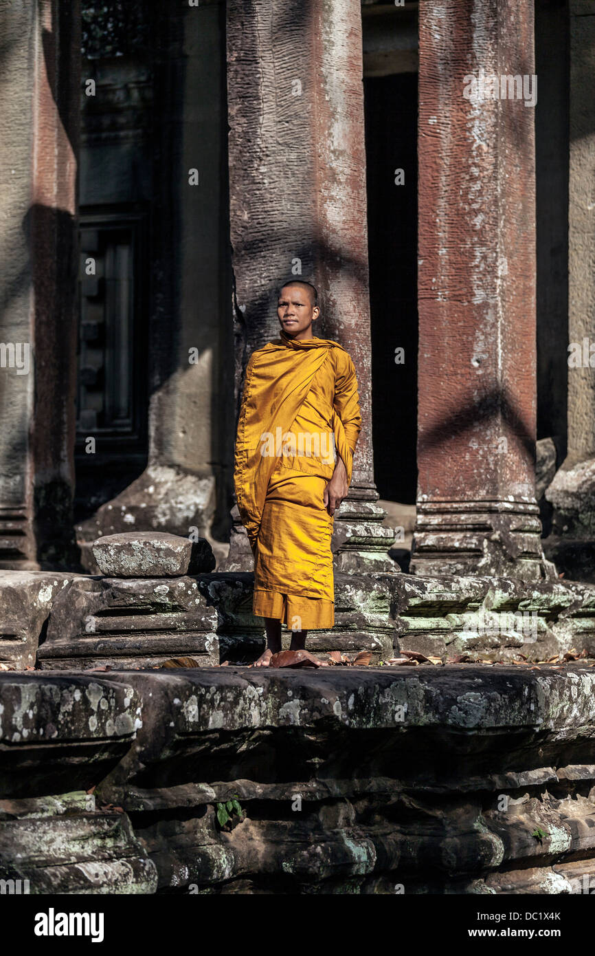 Young Buddhist monk praying outside temple in Angkor Wat, Siem Reap, Cambodia - Stock Image