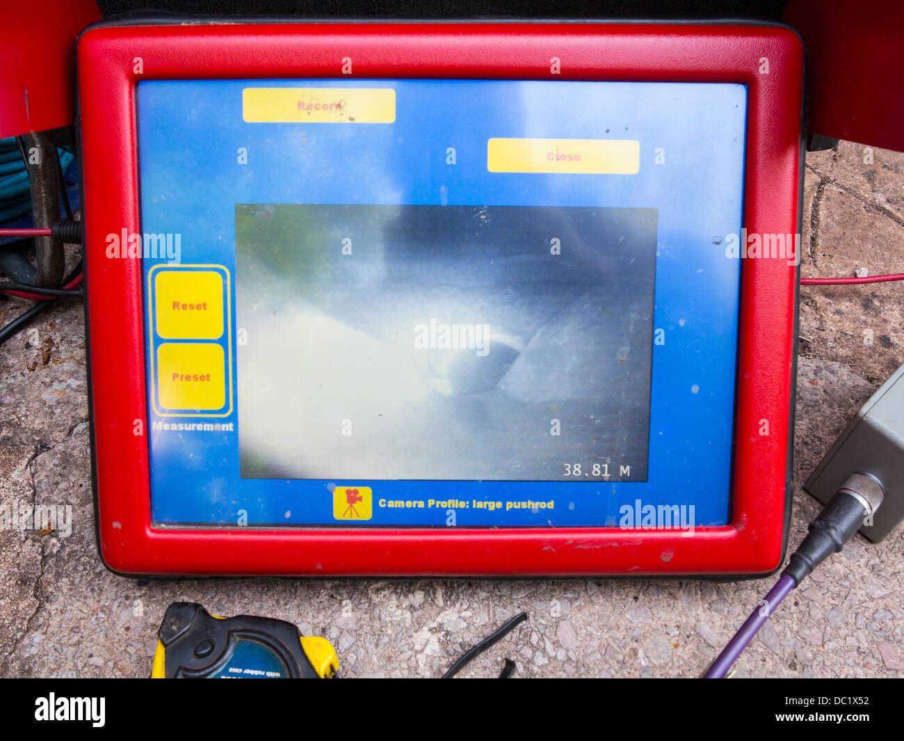 Sewer remote camera monitor showing damage and blockages in an underground sewer drain - Stock Image
