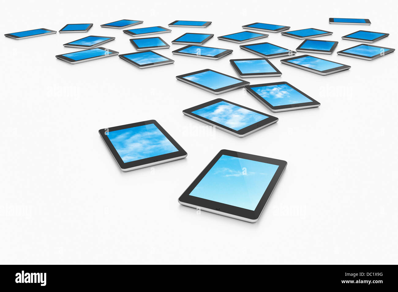 Large group of digital tablets displaying choice of blue skies - Stock Image
