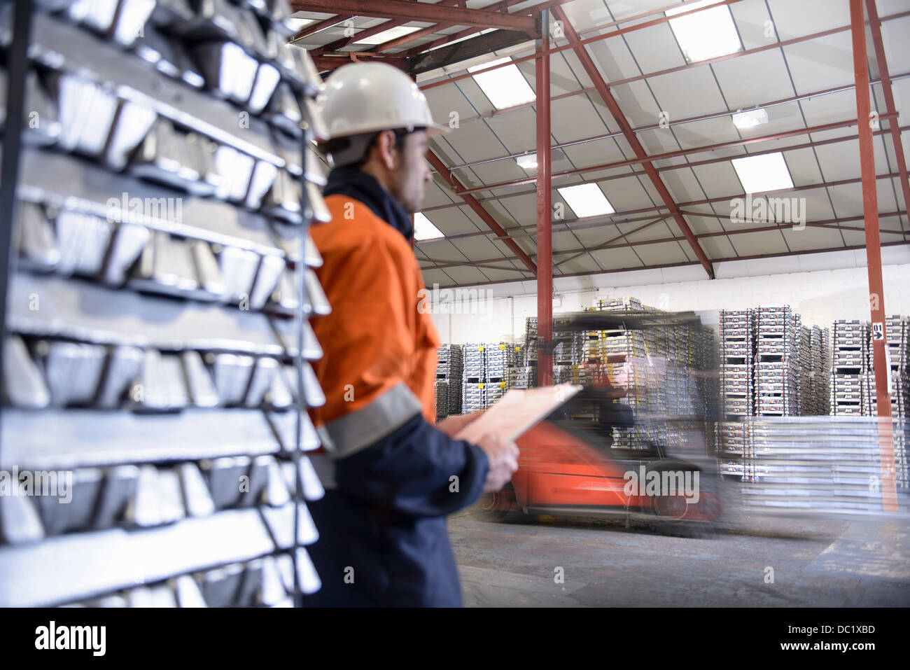 Warehouse workers moving stacked aluminum ingots - Stock Image