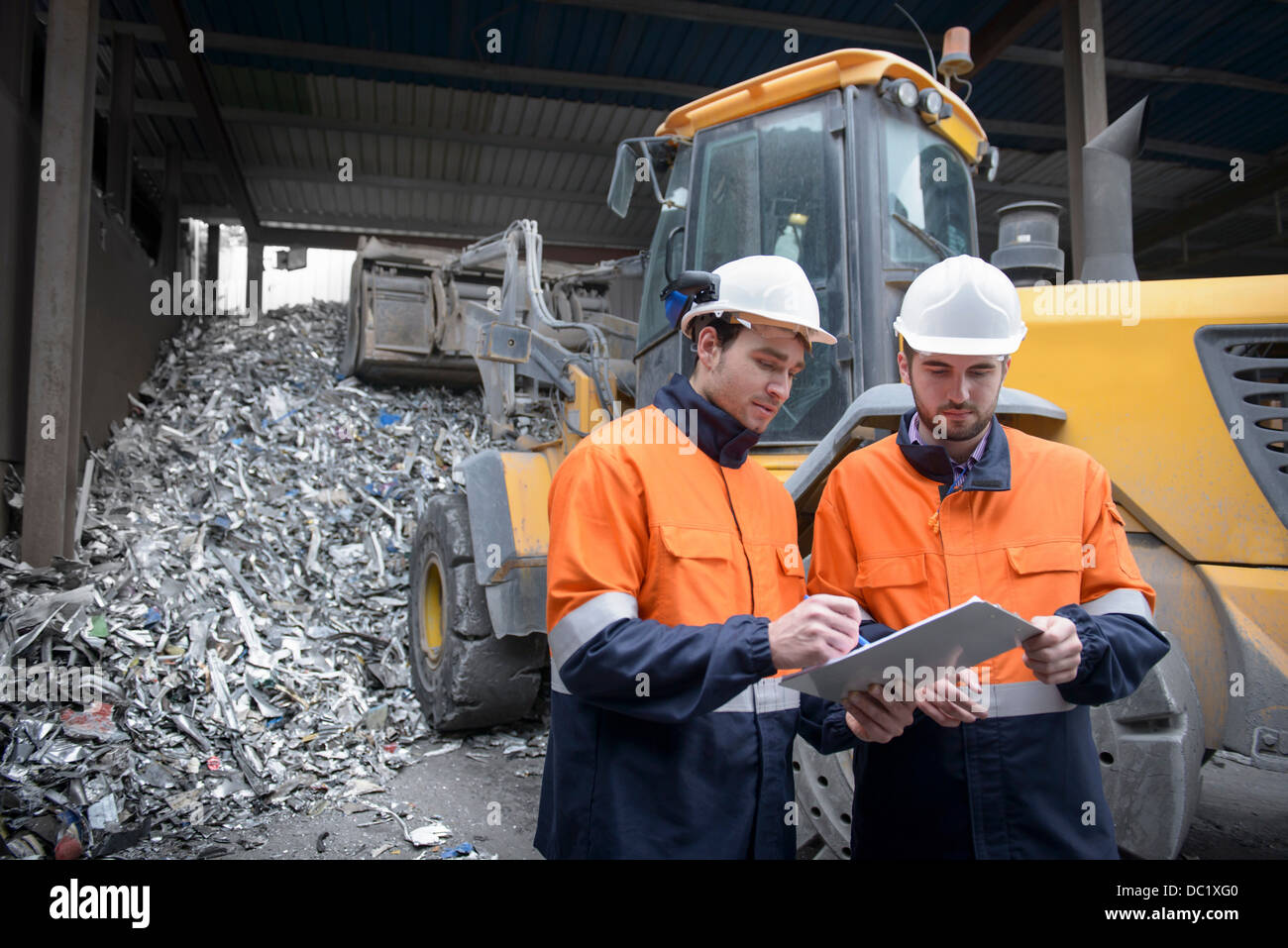 Workers checking clip chart in scrap metal yard - Stock Image