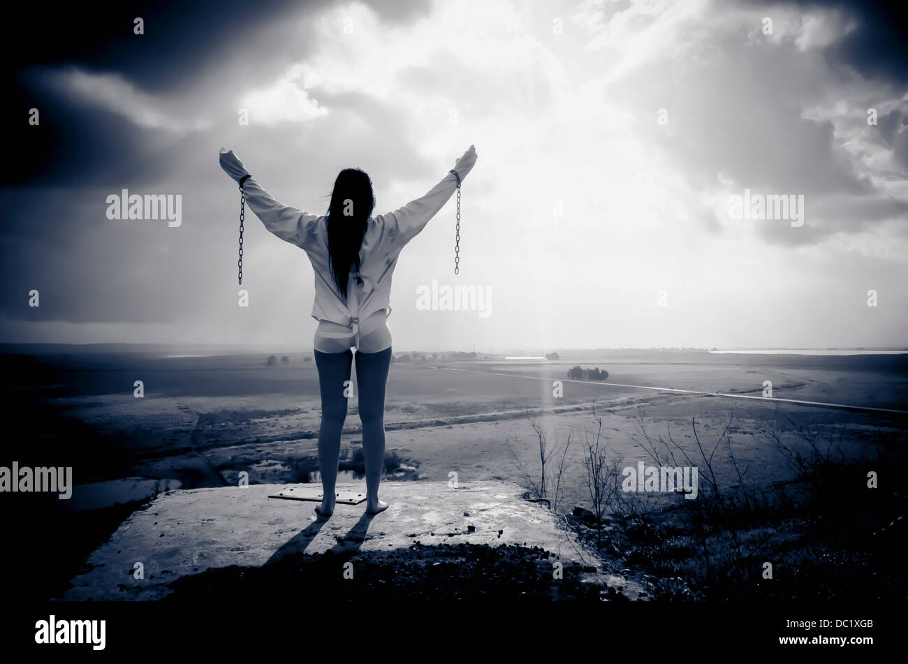 Woman wearing chains and straitjacket looking out over land - Stock Image
