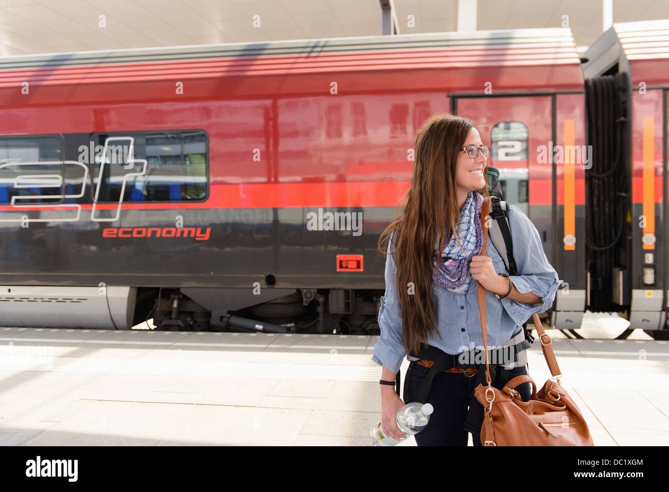 Female backpacker arriving in train station, Salzburg, Austria - Stock Image