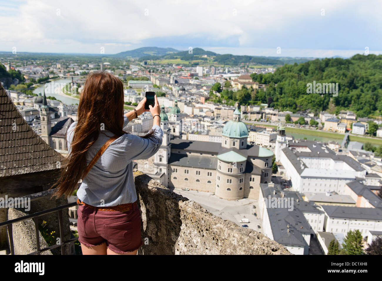 Female tourist photographing view of the city, Salzburg, Austria - Stock Image