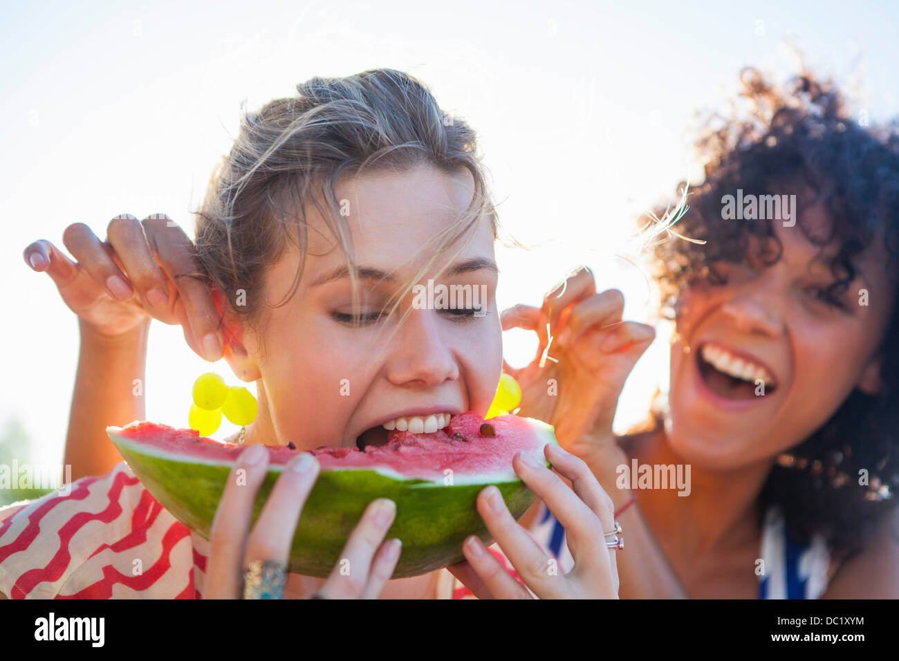 Young woman eating watermelon as friend pulls her ears - Stock Image