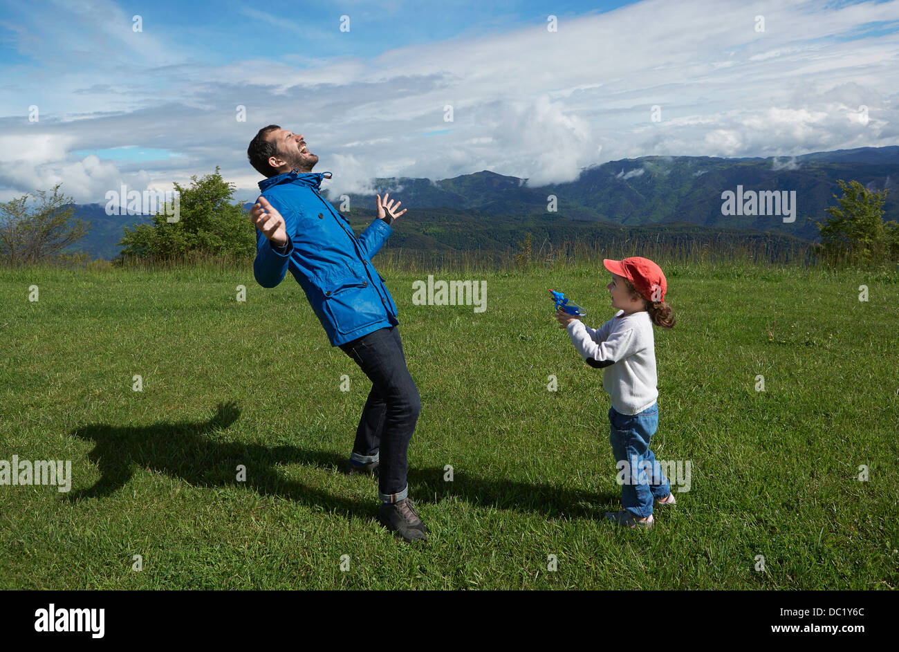 Father and young daughter play acting with toy gun Stock Photo