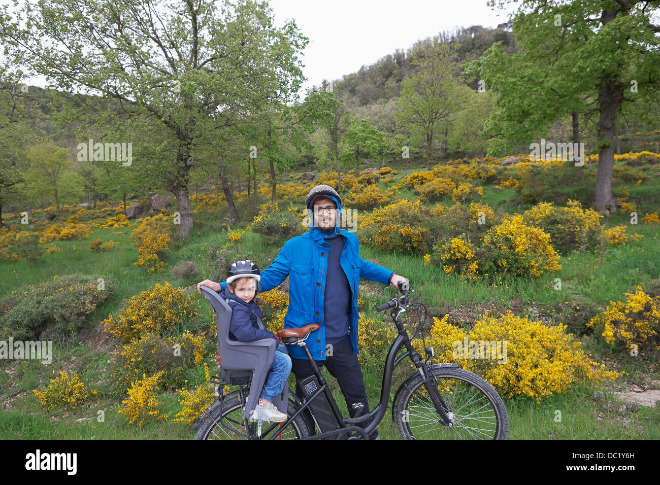Portrait of father and young daughter on bike - Stock Image